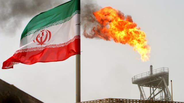 Iranische Flagge vor einer Flamme.