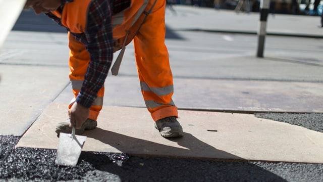 Ein Bauarbeiter streicht Teer auf eine Strasse.