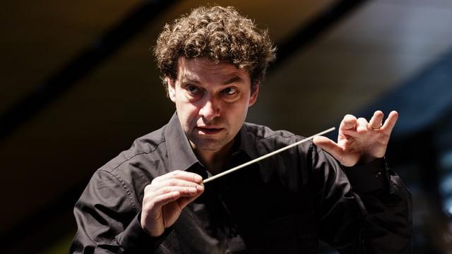 Dirigent mit Kraushaar und Dirigentenstab in der rechten Hand, sehr konzentriert