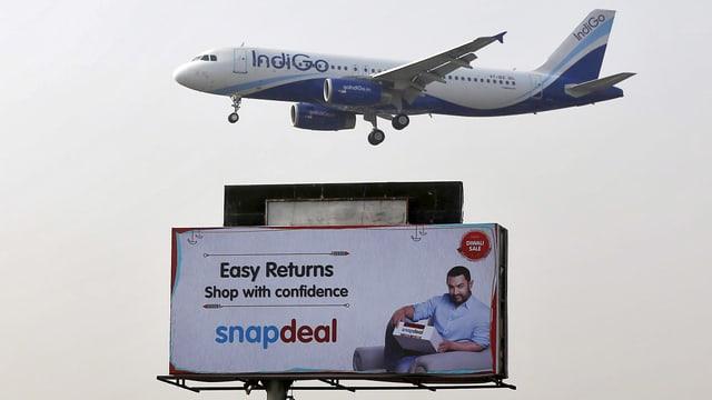 Ein Flugzeug fliegt über eine Werbetafel für einen Online-Händler.