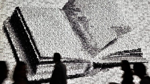 Silhouetten von Menschen vor einem riesigen, an die Wand projizierten Buch.