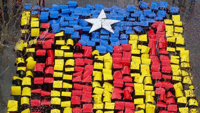 Mit roten, gelben, blauben und weissen Plakaten formen Katalanen ihre Regionalflagge auf einer Strasse (Aufnahme von oben).