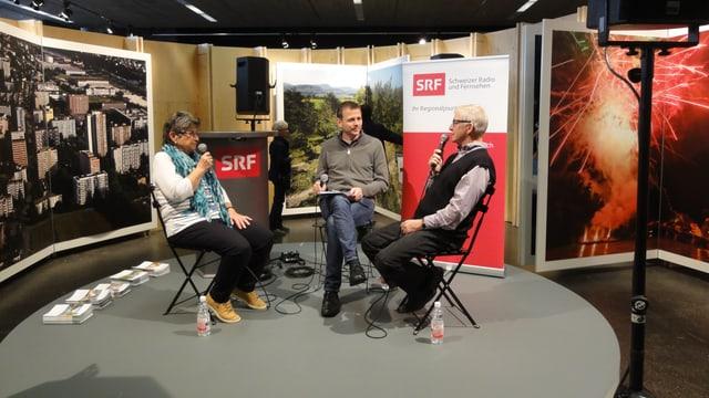 Drei Personen sitzen auf einer Bühne und sprechen miteinander. In der Hand haben sie ein Mikrofon.