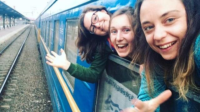 Drei junge Frauen schauen aus einem Zugfenster.