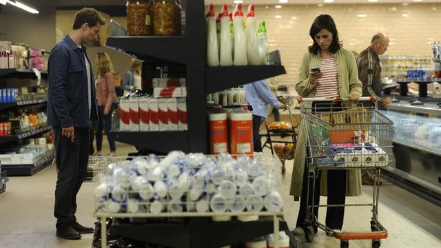 Ein Mann und eine Frau stehen auf verschiedenen Seiten eines Regals im Supermarkt. Sie schiebt einen Einkaufswagen und schaut auf ihr Handy.