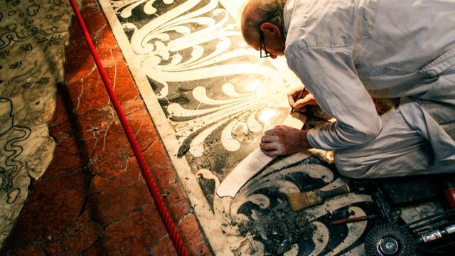 Ein Mann kniet auf dem Boden und restauriert die Marmorplatten.