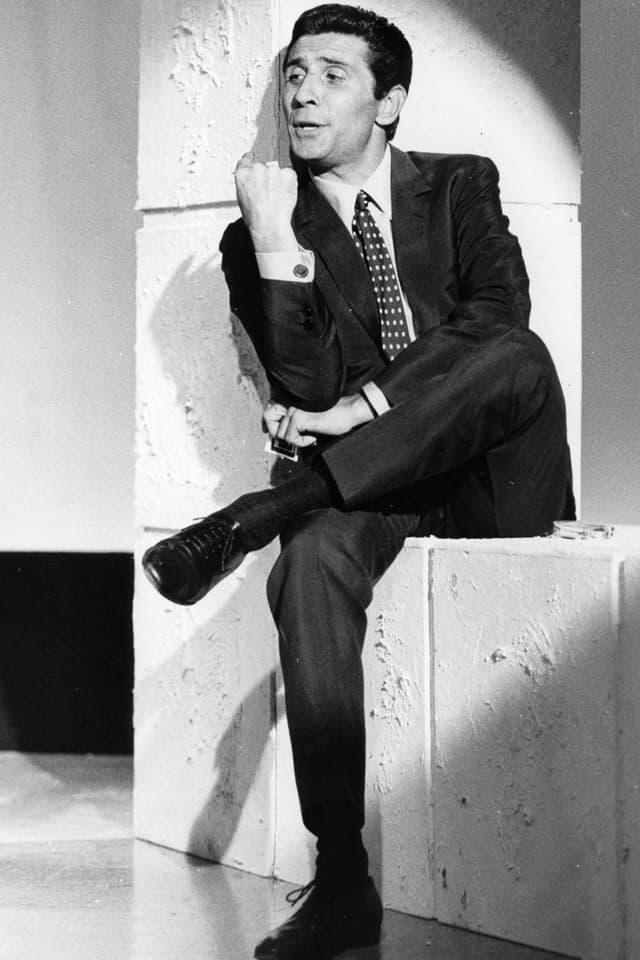 Ein Mann im dunklen Anzug sitzt auf einer weissen Mauer.