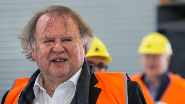 Ein älterer Herr mit orangefarbener Weste.