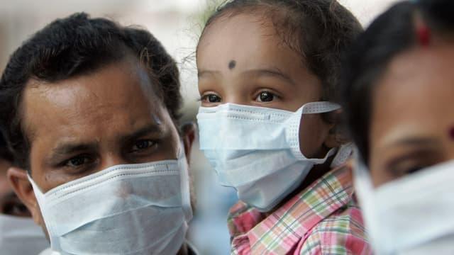 Inder mit weissem Mundschutz stehen im Jahr 2009 vor einem Spital Schlange für einen Untersuch auf H1N1-Viren
