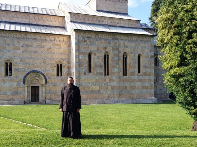Mönch mit langem Bart und schwarzem Gewand steht im Gras vor einer Kirche.