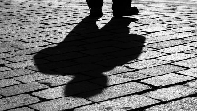 Auf Pflastersteinen ist der Schatten eines Mannes zu erkennen.
