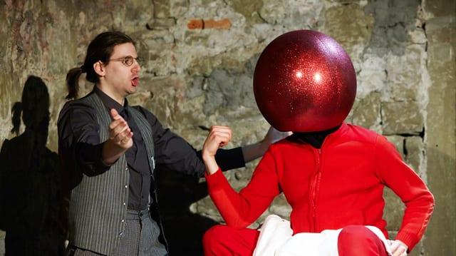 Mann in Anzug diskutiert mit einem Mann, der eine grosse Christbaumkugel als Kopf hat.