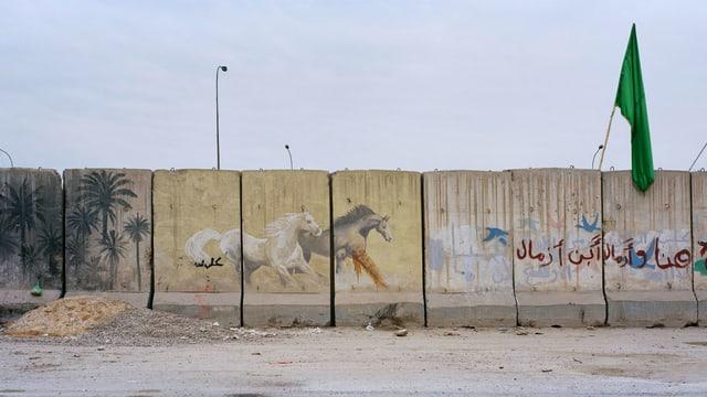 Eine Mauer, die mit Zeichnungen von Pferden und Palmen verziert ist