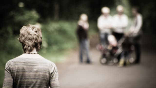 Ein Mann von hinten steht in der linken Ecke. Rechts von ihm steht (verschwommen) eine Familie mit Kinderwagen.
