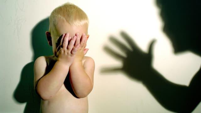 symbolbild. Kleines Kind hält die Hände vors Gesicht. Hand holt zum Schlag aus.