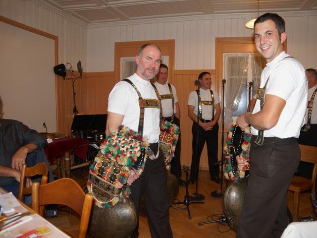 Zwei Männer in Trachten spielen mit ihren Glocken.