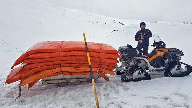 Ein Pistenpatrouilleur sammlt mit einem Schneefahrzeug gepolsterte Pistenabschrankungen ein.