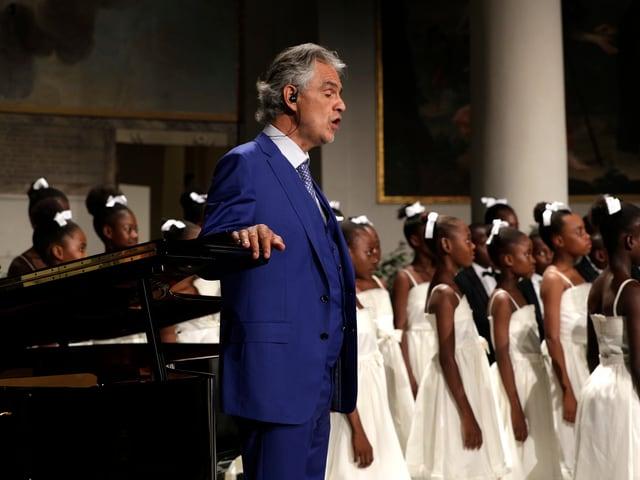 Mann in blauem Anzug am singen, Mädchenchor