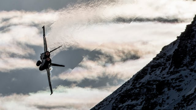 F/A-18 fliegt an Berg vorbei.