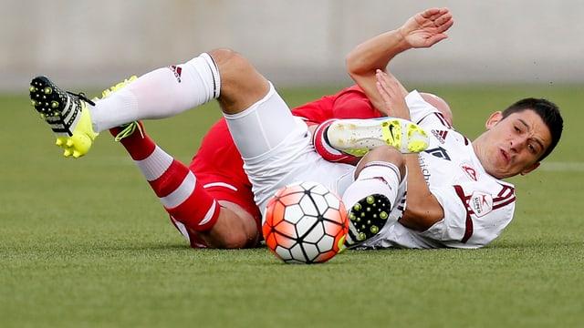 Fussballer liegen am Boden.