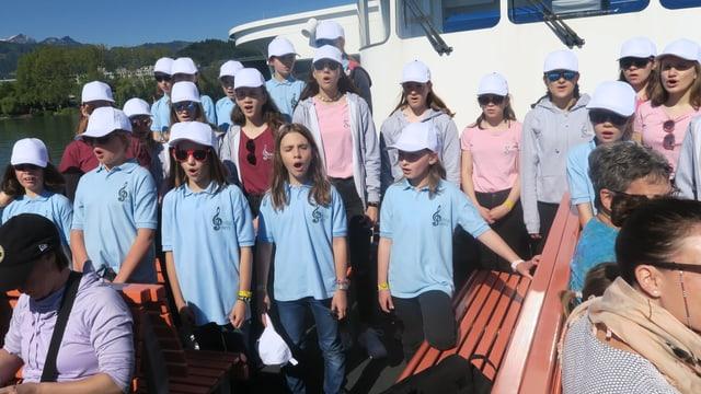 Kinder singen auf einem Schiff.