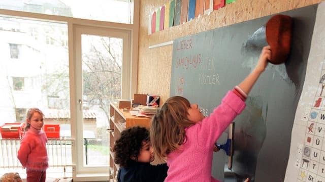 Kinder putzen die Wandtafel