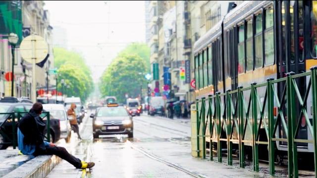 Ein Mann sitzt am Strassenrand, es regnet.