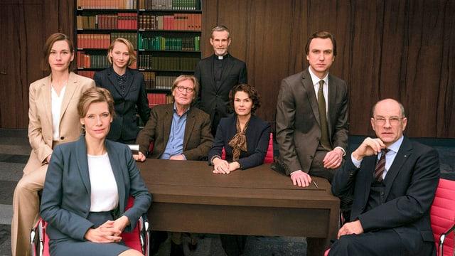 Acht Männer und Frauen sitzen um einen Tisch herum und schauen in die Kamera. Sie tragen Bürokleidung.