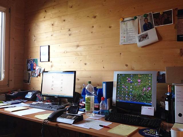 Ein Schreibtisch mit zwei Computern und vielen losen Blättern, einem Telefon und PET-Flaschen. Fotos an der Holzwand.