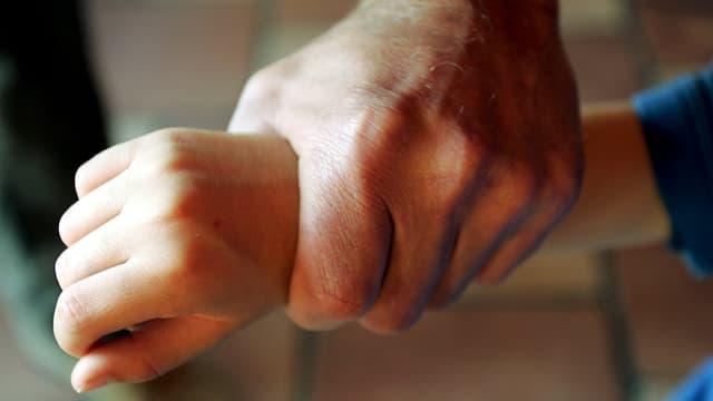 Männerhand umklammert Kinderhand.