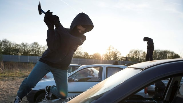 Ein Antifa-Aktivist schlägt mit einer Axt die Frontscheibe eines Wagens ein.