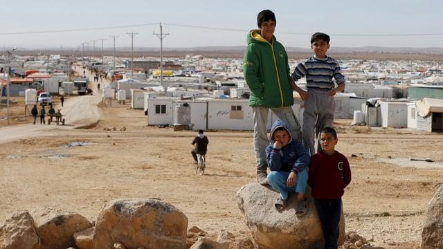 Im Vordergrund vier Kinder, im Hintergrund in wüstenähnlichem Gebiet ein Flüchtlingscamp aus Containern.