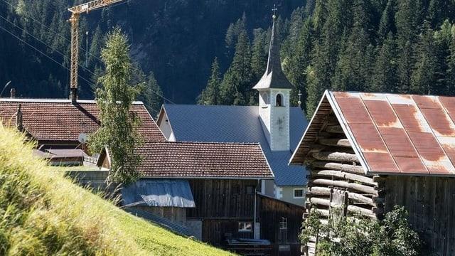 Hausdächer mit Kirchtrum, Wald im Hinergrund