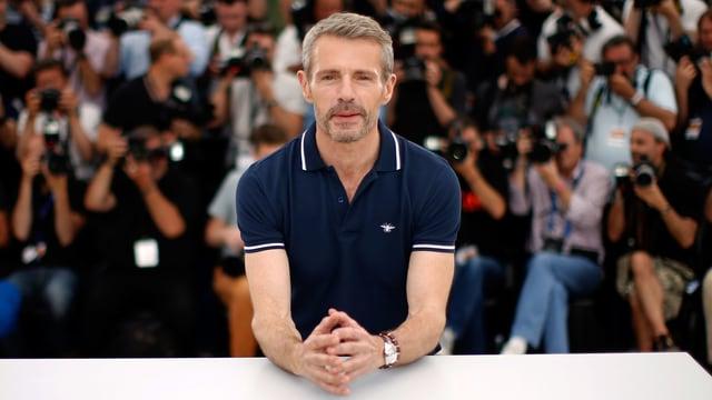 Schauspieler Lambert Wilson posiert an einem Festival lässig für die Kamera.