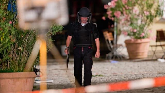 Ein Polizist in Ansbach am Tatort hinter Absperrungen.
