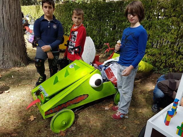 Drei Jungs stehen um eine grüne Seifenkiste, die eine Zunge, Augen und einen grossen Mund hat.