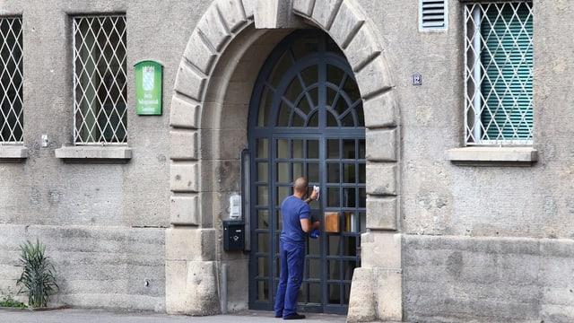 Ein Mann putzt das Tor der Strafanstalt Landsberg.