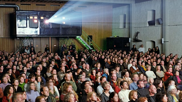 Ein voller Kinosaal. Die Leute sehen auf die Leinwand.