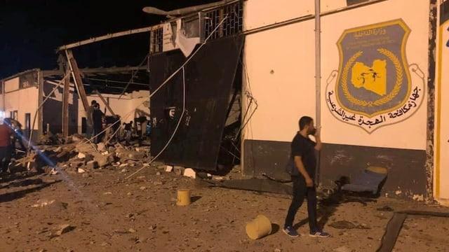 Ein Mann telefoniert vor einem zerstörten Gebäude des angegriffenen Flüchtlingslagers