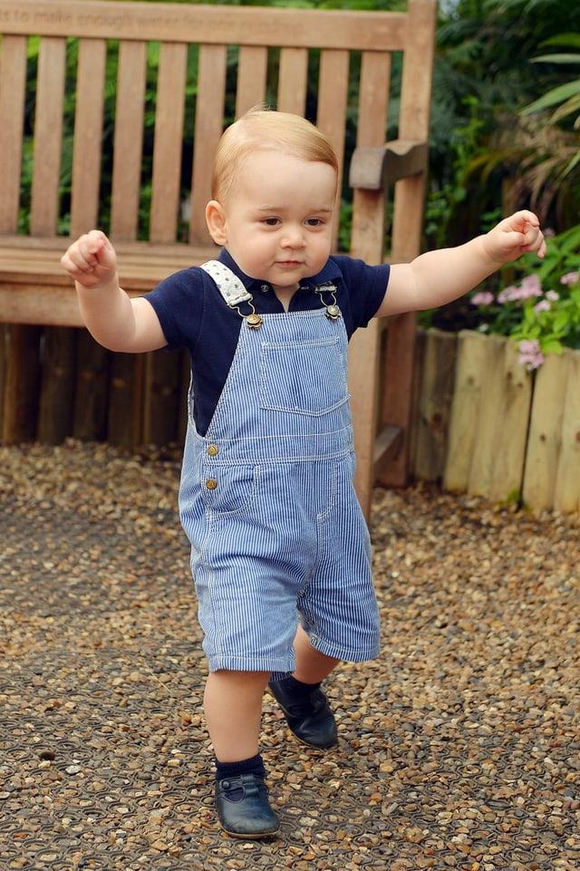 Prinz George in blauen Latzhosen gehend.