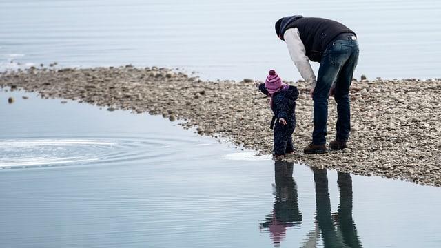 Ein Mann steht mit einem Kiesel werfenden Kind am Ufer eines Sees.