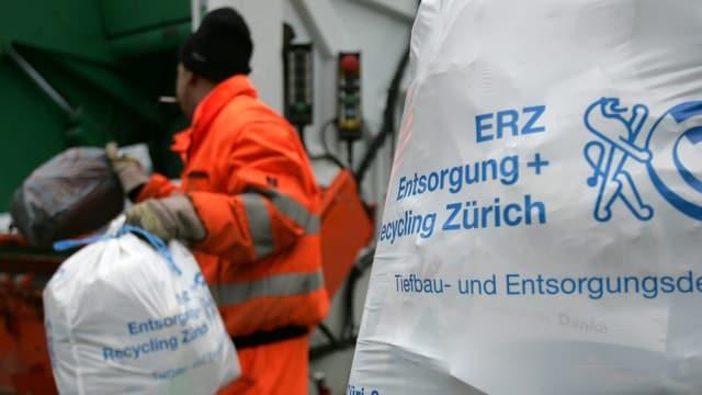 Ein Zürcher Müllsack, weiss mit blauer Aufschrift «ERZ Entsorgung + Recycling Zürich», wird von einem Angestellten in orangem Gewand eingesammelt.