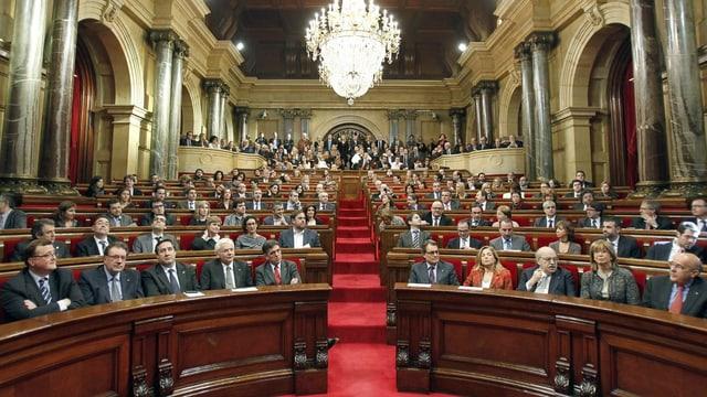 Menschen sitzen in einem Parlamentssaal.