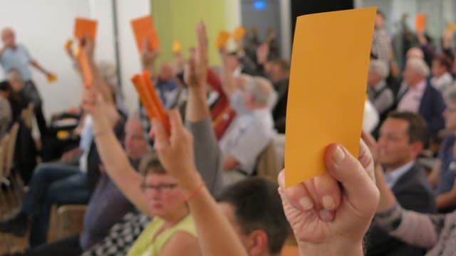 Im Vorgdergrund eine Hand, die einen orangen Zettel in die LKUft hält. Im Hintergrund in der Unschärfe andere Menschen, die teils einen Zettel hochheben und teils nicht.