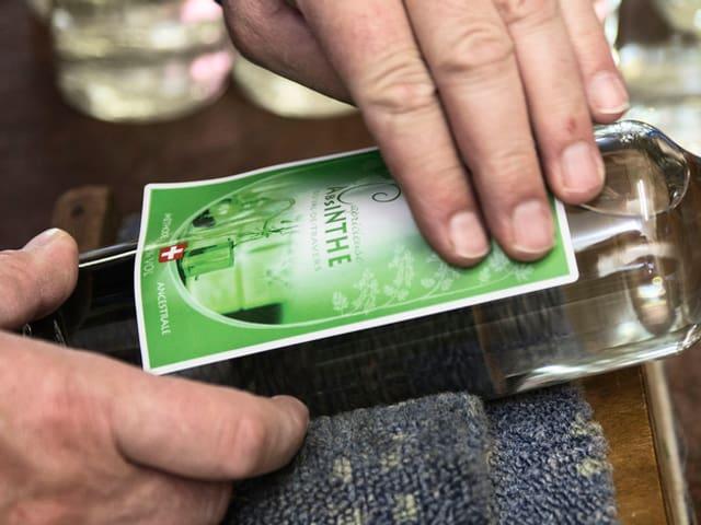 Hand klebt Etikette auf Flasche.