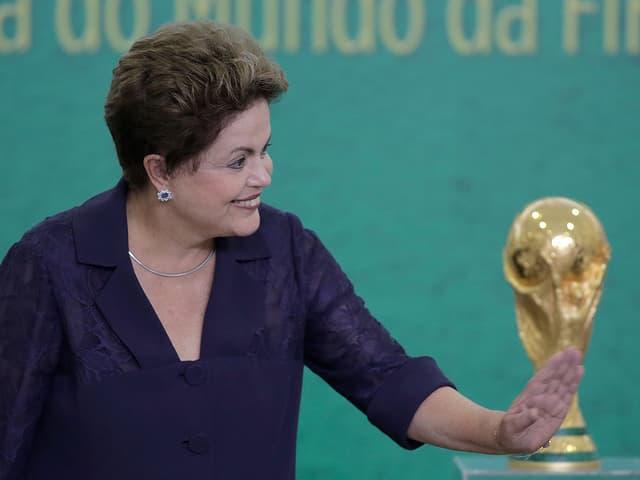 Dilma Rousseff lachend, im Hinergrund der WM-Pokal.
