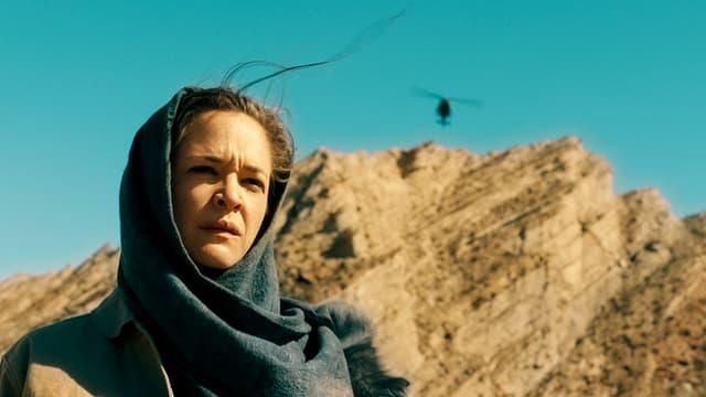 Frau in Wüste, ernst blickend mit Tuch um den Kopf gewickelt