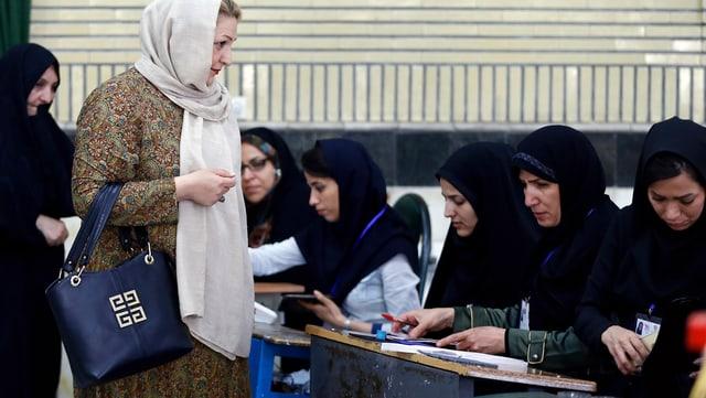 Eine Frau bei der Stimmabgabe in einem iranischen Wahlbüro.