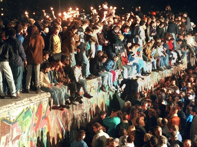 Jubelnde Menschen sitzen und stehen mit Wunderkerzen auf der Berliner Mauer.