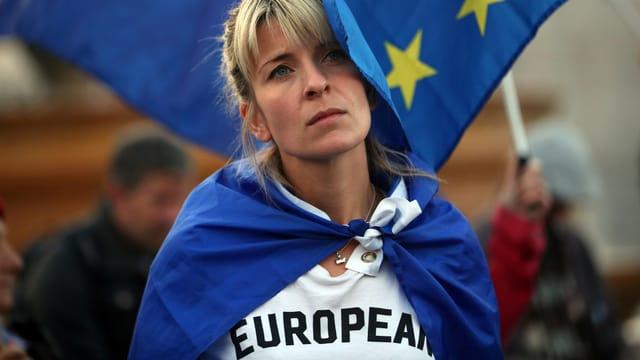 Eine Frau in weissem T-Shirt mit Überschrift «European», vor einer EU-Flagge.
